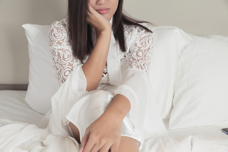 Lonely and depressed sad woman in silk nightgown and lace robe with hands on face, Sad depressed thoughtful asian woman feeling bad at bedroom Stok Fotoğraf