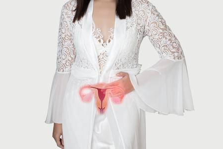 Frau in weißem Seidennachthemd und Spitzenrobe mit Uterusschmerzen in der Nacht. Menschen mit Bauchschmerzen. Abbildung der Gebärmutter ist auf dem weiblichen Körper