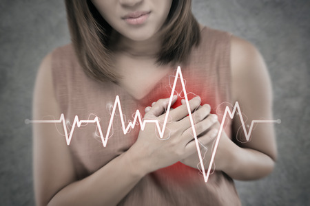 The Asian woman suffering from chest pain on a cement wall background. People having heart disease or heart attack. Hands pressing on the chest with a painful Because of Severe angina symptom Stok Fotoğraf