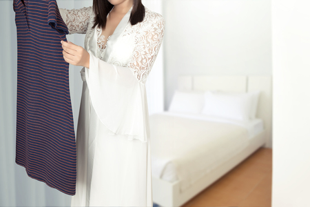Asian woman in long white silk nightgown stand choosing clothes in wardrobe at home