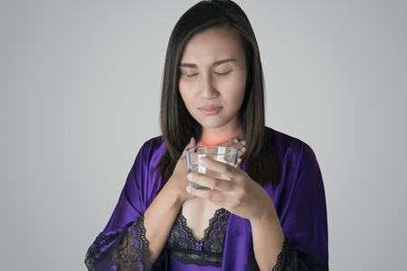 Thailand women in purple silk nightwear and purple robe holding a glass of water have a sore throat due to the dry throat at night. Asian women drinking water because of the dry throat on a gray background