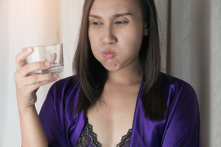 Asian woman in silk nightwear and silk purple robe drinking water against a gray background, People Rinsing And Gargling While Using Mouthwash From A Glass - Dental Healthcare Concepts