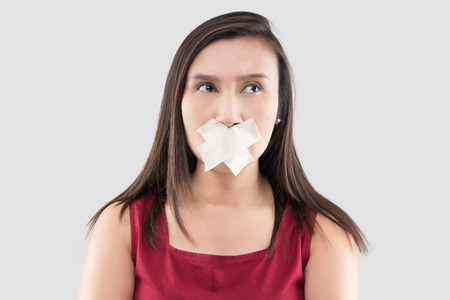 Asian women in red dresses use masking tape to close the mouth because they do not want to comment on a gray background, Thai female in with adhesive tape over his mouth, Stop talking Stok Fotoğraf