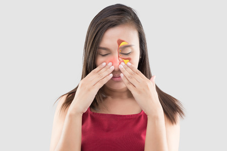Asian woman in red wear feeling unwell because of sinus against a gray background. People caught a cold and fever. The concept of healthcare and allergy Stok Fotoğraf