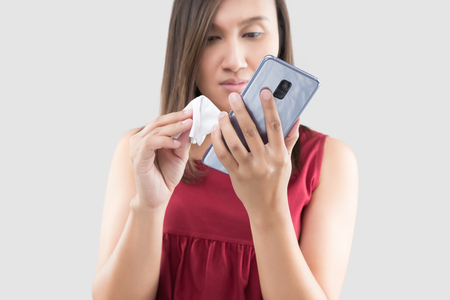Asian hands woman cleaning her mobile phone on screen with the microfiber cloth on a gray background. Lady is wiping the body of the smartphone with a microfiber cloth.