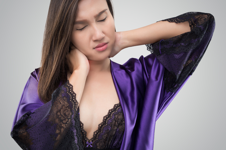 Asian woman in the silk nightwear and purple robe who is having pain in her neck on a gray background, Thailand people having pain in the back and neck at night