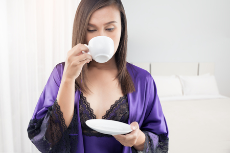 The woman in silk nightwear and purple lace robe with a cup of hot coffee at the bedroom in the morning, Sexy girl in the morning with a white cup of tea in bed in a violet nightgown.