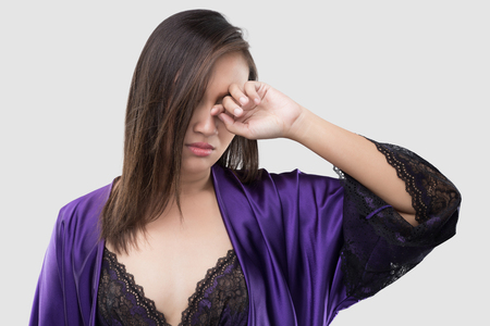 The woman in silk purple nightgown and lace robe rubs her eye with a finger against the gray background, Women in violet satin nightwear have itching in the eye