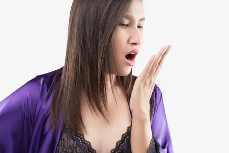 The woman in silk nightgown and purple robe checking her breath with hand on a gray background, Halitosis concept of a woman with bad breath, Bad breath