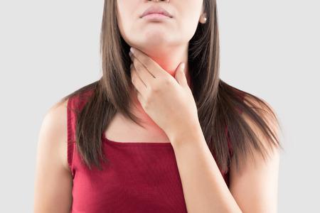 Mujer asiática con dolor de garganta o glándula tiroides contra el fondo gris. Reflujo ácido o acidez estomacal, dolor de cuello, concepto de problema corporal de personas Foto de archivo