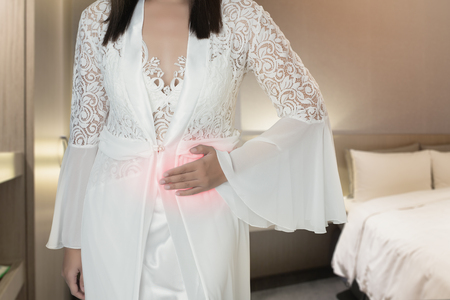 The woman in silk nightwear and white robe wake up for go to the bedroom, Women with menstrual disorders at night, Menstrual cramps, Irritable Bowel Syndrome or IBS Stok Fotoğraf
