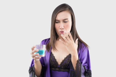 Asian woman in sexy silk nightgown and purple robe feel burn in her mouth because using mouthwash against a gray background, Wash the mouth, Female rinsing and gargling while using mouthwash from a glass
