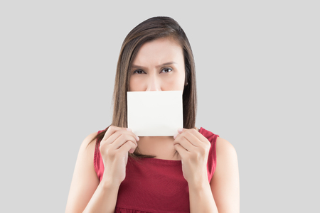 A woman in the red shirt holding the blank white card with space for text in front of his mouth against the gray background Stok Fotoğraf