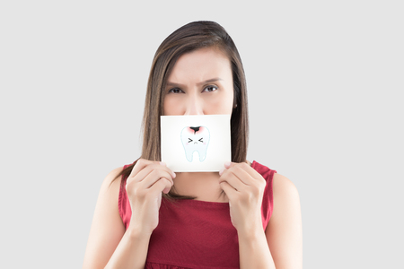 Asian woman in the red shirt holding a white paper with the caries cartoon picture of his mouth against the gray background, Have a toothache, The concept with healthcare gums and teeth