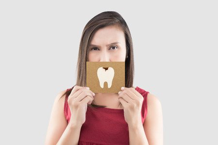 Asian woman in the red shirt holding a brown paper with the caries cartoon picture of his mouth against the gray background, Have a toothache, The concept with healthcare gums and teeth Stok Fotoğraf
