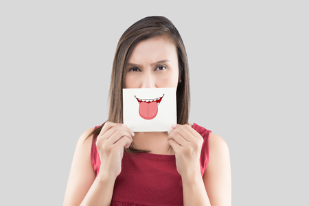Asian woman holding a paper with a cute tongue face on it in front of her mouth
