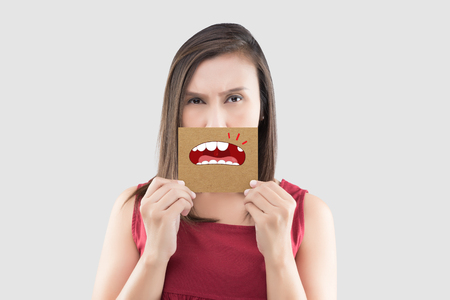 Asian woman in the red shirt holding a brown paper with the broken tooth cartoon picture of his mouth against the gray background, Decayed tooth, The concept with healthcare gums and teeth Stok Fotoğraf