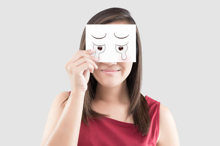 Asian woman holding a white paper with a cartoon cry face on it in front of her eyes against the gray background