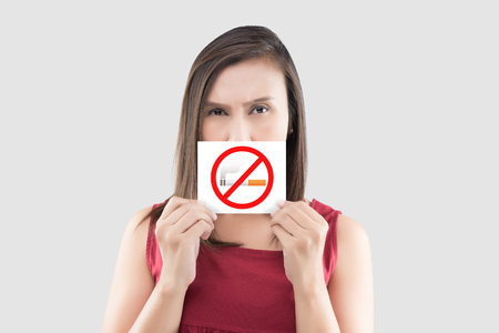 Asian woman in red blouse is holding no smoking sign on the white paper against gray background. Picture of the woman with a smoking restriction sign. Warning about the harm of tobacco use at the public place.