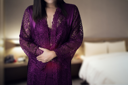 Woman in white silk nightgown and lace robe with uterus pain at night. inflammatory bowel disease. People having stomach ache