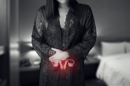 Woman in white silk nightgown and lace robe with uterus pain at night. People having belly ache. illustration of uterus is on the female body Stok Fotoğraf