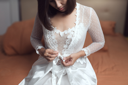 Woman wearing a long white nightgown and bow tie on a white silk robe with lace sleeve in the bedroom at night. Asian woman trying on new white nightwear for sleep