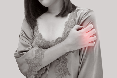 Asian women who are itching from insect bites against gray wall background.  Health care and medicine.  People with skin problem concept