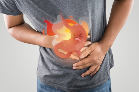 The photo of cartoon stomach On mans body against white background, Acid reflux disease symptoms or heartburn, Concept with healthcare and medicine