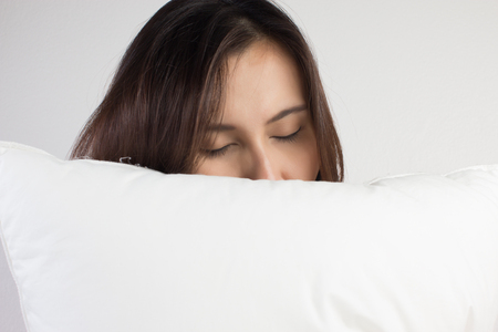 woman sleeping well in bed hugging soft white pillow Stok Fotoğraf