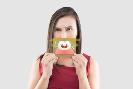 Asian woman in the red shirt holding a brown paper with the yellow teeth cartoon picture of his mouth against the gray background, Bad breath or Halitosis, The concept with healthcare gums and teeth Banco de Imagens - 132125558