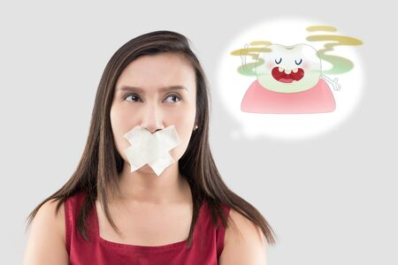Asian woman in the red shirt holding a brown paper with the yellow teeth cartoon picture of his mouth against the gray background, Bad breath or Halitosis, The concept with healthcare gums and teeth Stock Photo