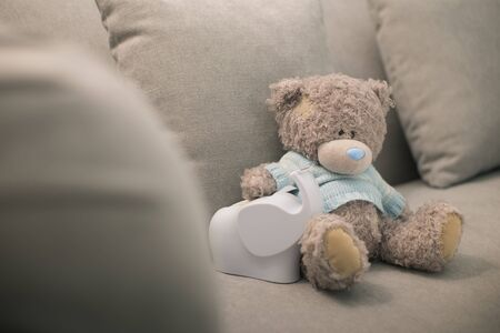 Lonely teddy bear and elephant doll is on the brown sofa. Lonely doll Zdjęcie Seryjne - 132125583