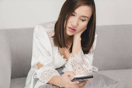 Asian woman wears a white nightgown and Long sleeve satin robe with floral lace on the sofa late at night texting using mobile phone sleepless and smartphone addiction in internet communication. Insomnia and social media addiction concept.