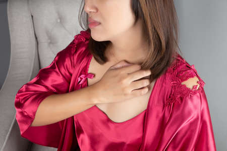 Asian women in the red nightwear are scratching their chest due to itching. People itching body. The concept of allergy symptoms and healthcare 版權商用圖片