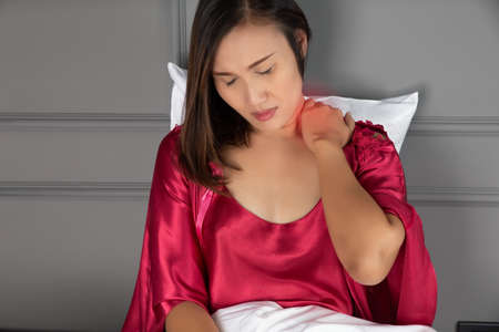 Neck pain and Shoulder pain in a woman, Ache pinched nerve in the neck or shoulder, Women wear red nightgown & Short sleeve satin robe with floral lace stiff neck when waking up in the morning
