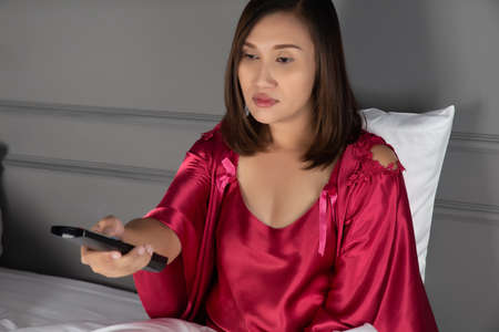 The woman is sleepy while she is watching television in the bedroom at night, Asian girl wearing nightgown and satin robe with insomnia