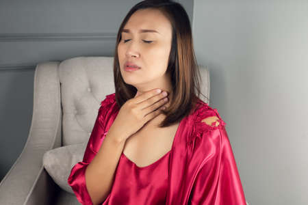Sore throat pain symptoms. Throat infection. A woman wearing a satin nightgown and red robe suffering from hoarseness or laryngitis in the living room at night. 版權商用圖片