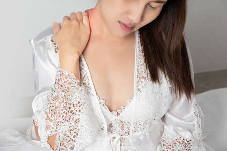 Shoulder pain or Dislocated shoulder in a woman, Ache pinched nerve in the neck or shoulder, Women wear white nightgown & long sleeve satin robe with floral lace have neck pain in the bedroom at night 版權商用圖片