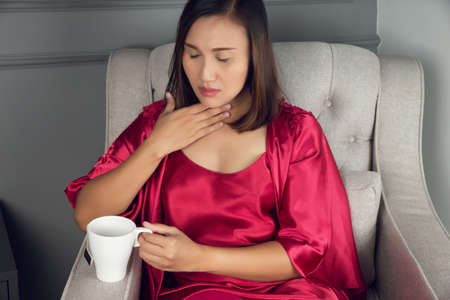 A sore throat is a pain, Scratchiness, or irritation, Asian women in red silk nightwear with acid reflux at night, The concept of healthcare and medicine.