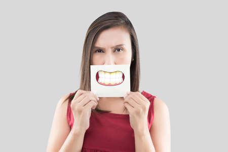 Asian woman in the red shirt holding a brown paper with the Dental plaque cartoon picture of his mouth against the gray background, Bad breath or Halitosis, The concept with healthcare gums and teeth