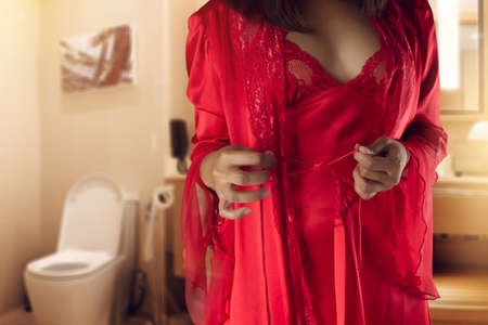 The woman in red nightgown & long sleeve satin robe with floral lace wake up for go to restroom, Nocturia or frequent urination at night. Stockfoto