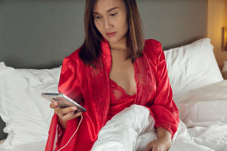 Smartphone Addiction, Asian woman sitting on the bed at night in a satin nightgown and red robe with a mobile phone in the bedroom. Girl in sleepwear using a smartphone late night because sleepless