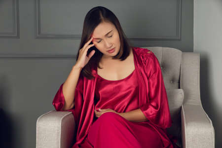 A woman having a headache. Asian lady in a red nightgown and satin robe dizzy until insomnia on the gray sofa in the bedroom at night.