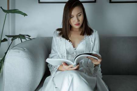 A woman in a cozy nightgown reading a book while resting on the living room at home. Girl in white nightwear and wore long sleeve satin robe with floral lace late night sleeping because of insomnia.