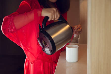 The woman wore red satin long robe making tea in the kitchen at night. Asian girl pour hot water into a white cup