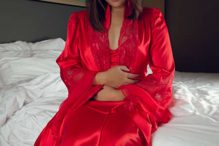 Irritable Bowel Syndrome or IBS. Asian woman in a silk nightgown and red robe suffering from period cramps while sitting on the bed in bedroom at night. Girls are not sleeping because of stomach pain.