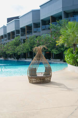Wicker chairs beside the property's swimming pool in Phetchaburi city in Thailand