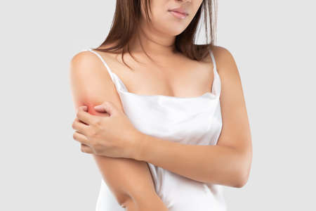 A woman in the white satin dress is scratching their upper arms due to itching on a gray background. Female with dry skin. The concept of dermatitis symptoms and skin care