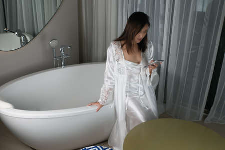 Asian woman sitting on the bathtub at night in a white nightgown and silk robe with a mobile phone in the accommodation. Smartphone Addiction. Sleepless