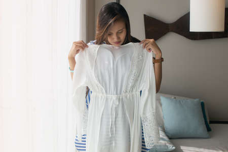 Asian woman choosing silk robe in an accommodation. A girl trying on new white robes for nightwear at home. 版權商用圖片